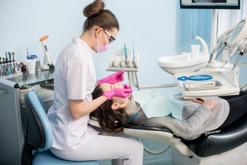 a woman in the dentist chair with a dental hygienist working on her teeth