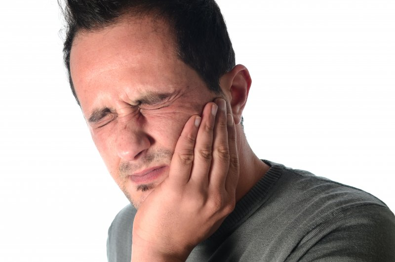 young man frowning from tooth pain