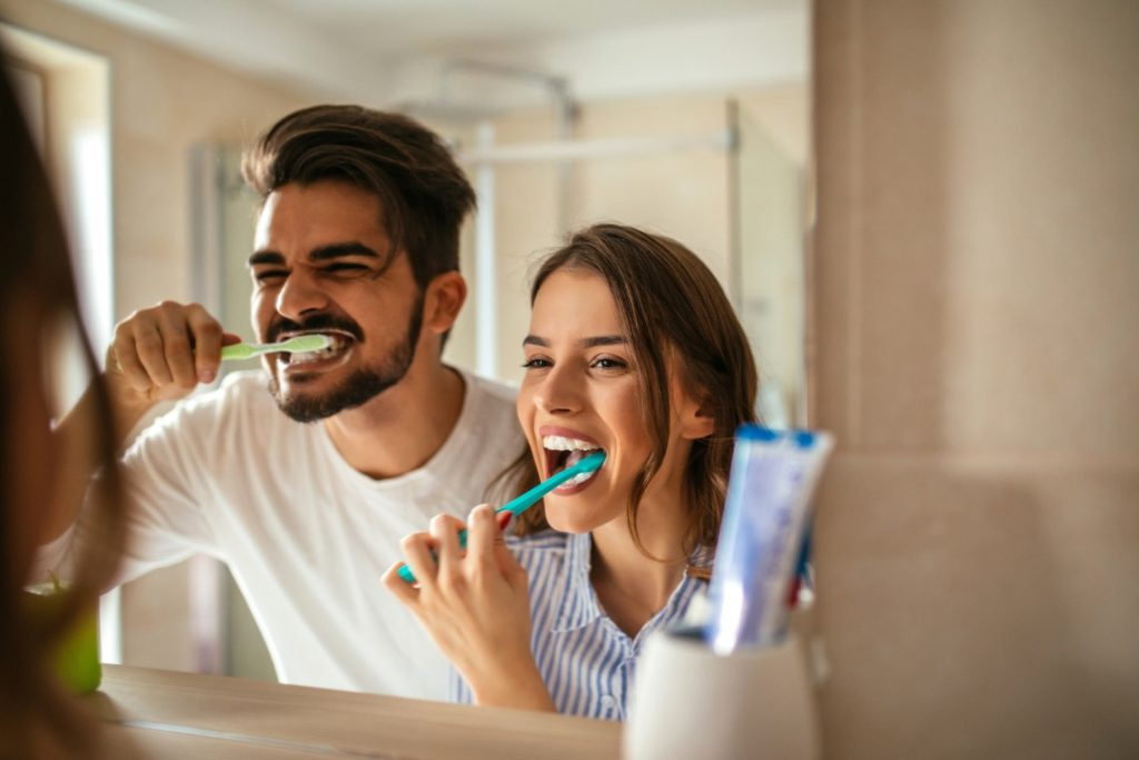 A man and woman brushing their teeth with tips from a dentist