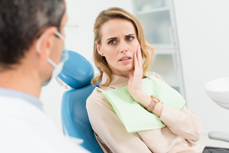 Female patient talking to dentist about toothache