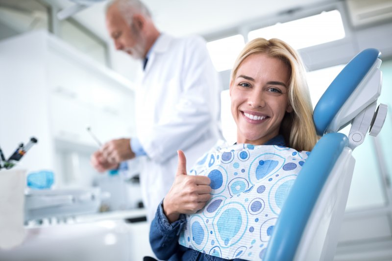 Woman giving thumbs up at dental checkup